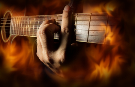 retro music: Playing acoustic guitar with fire flame screen,music concept.