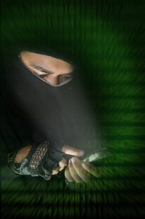 Hacker using smart phone with digital code screen.