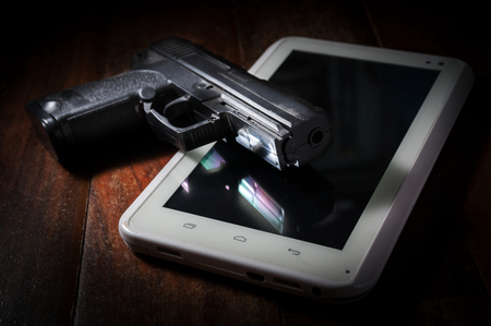 agent de s�curit�: Hand gun on computer tablet Banque d'images