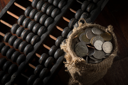 economic revival: Still life Abacus with coins in gunny sack. Stock Photo