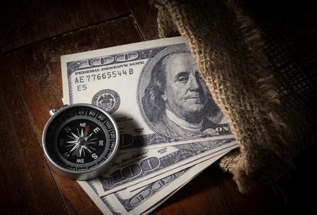 gunny: Still life Compass with money in gunny sack.