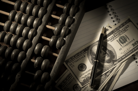 economic revival: Still life Abacus with pen and money on book.