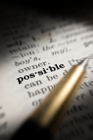 possible: Closeup Possible word in book with pen.