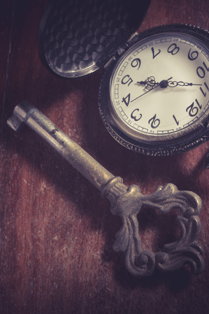 speculation: Old key with pocket watch,vintage color filtered.