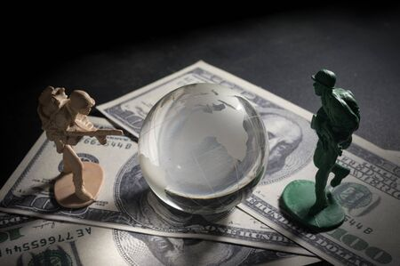 green plastic soldiers: Soldier toys and glass globe on money ,war concept. Stock Photo