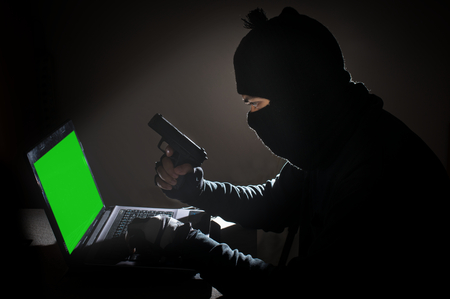 cyber terrorism: Robber man hack computer and hold gun.