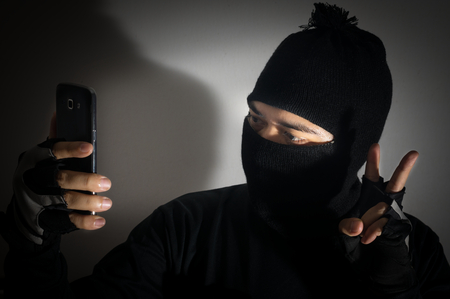 cyber terrorism: Robber man self portrait with phone camera.