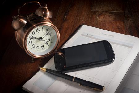 reloj despertador: Naturaleza muerta teléfono inteligente y pluma en el libro plan con el reloj de alarma.