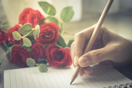 Donna scrittura a mano sul libro con la rosa, annata filtrata.