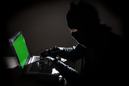 spy ware: Robber man hacking computer,crime concept.