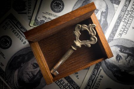 Old key and wooden chest on money,business concept.