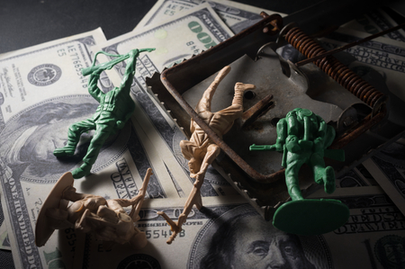 enticement: Soldier toys with mouse trap on money,war concept.