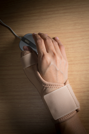 throbbing: Female hand with hand-support and mouse. Stock Photo