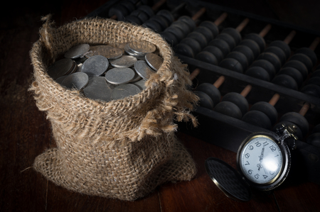 economic revival: Coins in gunny sack with pocket watch and abacus. Stock Photo