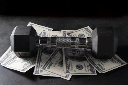 Metal dumbbell on dollar bill.