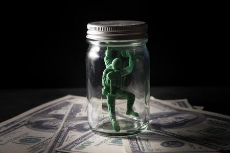 constrain: Soldier doll in bottle on money.