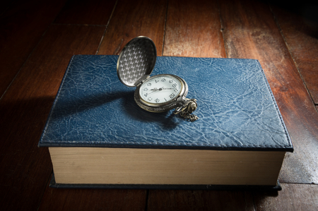 hard cover: Pocket watch on hard cover book,still life.