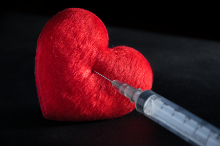 immunize: Red heart with syringe,medical concept.