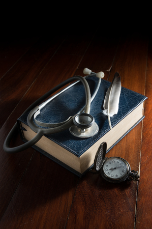 scientific literature: Still life Stethoscope with feather on book and watch.