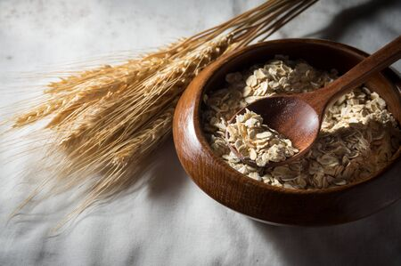 Rolled oats and wheat in wooden bowl with spoon Stock Photo