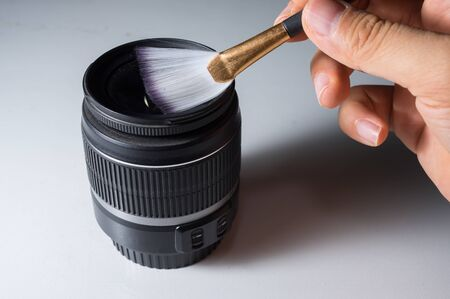 scuff: Cleaning camera lens by brush.