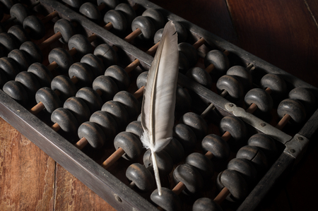 old desk: Feather on old wooden abacus.