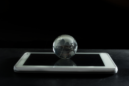 wold map: Glass globe with computer tablet. Stock Photo