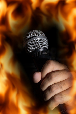 Microphone in hand with fire flame screen.