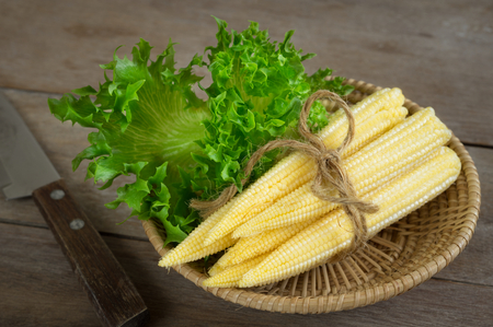 Baby corn with green vegetable in basket.