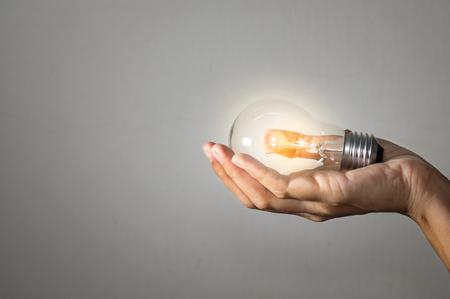 여자 손, 개념 아이디어에 전구입니다.