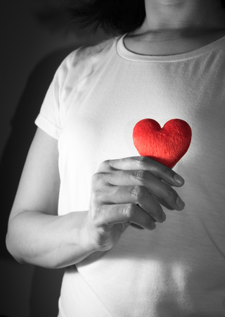 Red heart in woman hand.