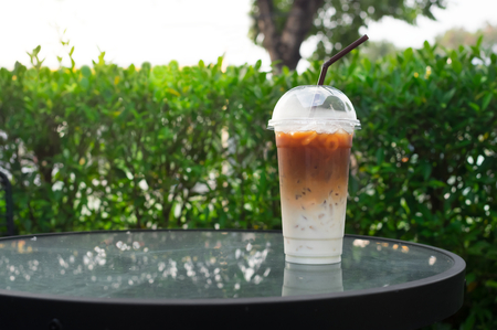 Iced coffee glass on wood table,with nature background.