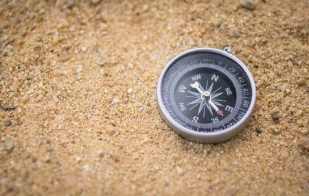 Compass on sand floor, navigation concept.