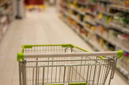 Shopping cart in supermarket,blur focus on shelve.
