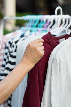 Woman choosing shirt in shop
