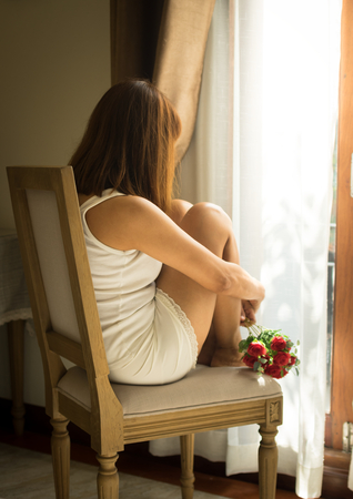 Woman sitting on chair and looking out window. Stock Photo