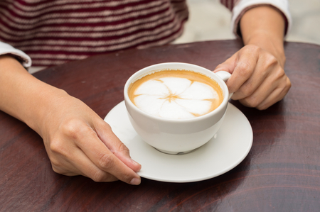 Woman holding hot  coffee cup in hand.