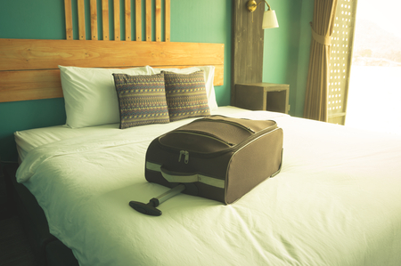 Suitcase on bed in hotel room,vintage filtered. Stock Photo