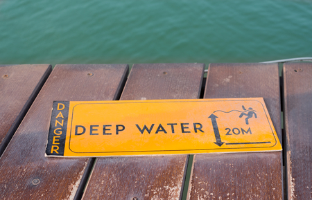 Deep water warning sign nearly to lake. 版權商用圖片