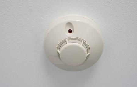 Plastic fire alarm detector in room ceiling.