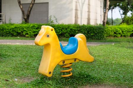 Yellow fastener horse seat for children in playground.