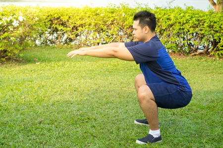 Asian man doing squat exercise in park.