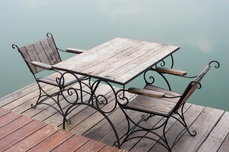 Wooden table and chairs nearly lake.