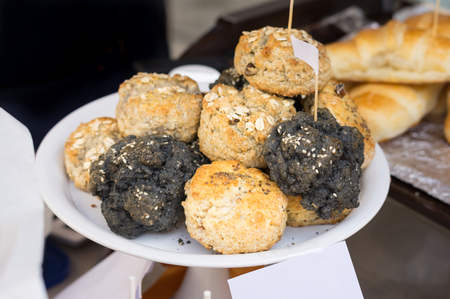 Brown and black scones on plate in market. Stock Photo