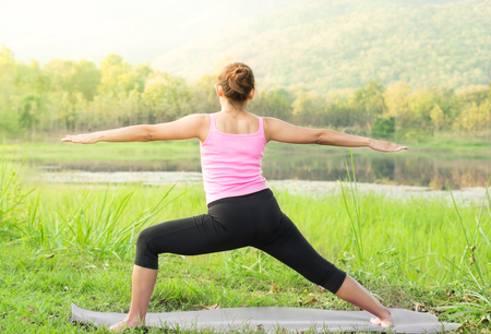 Woman practicing yoga, standing in warrior pose. Stock Photo