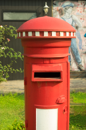 Ancient red mail post box on outdoor location. Stock Photo