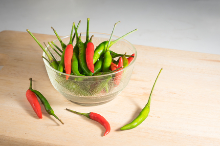 Fresh red and green chili pepper in bowl .