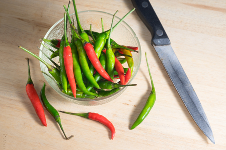 Fresh red and green chili pepper in bowl with kitchen knife. Banco de Imagens