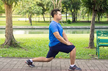 Asian man doing lunge exercise in park.