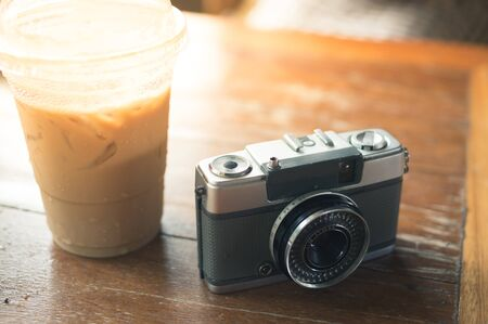 Retro camera with iced coffee on table.